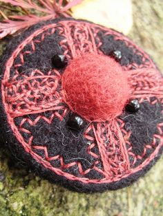 VIKING ART INSPIRED SHIELD BROOCH PRIMITIVE, ANCIENT, MAGIC SYMBOLS...FORGOTTEN ART FROM FAR NORTH...ROUND FIBULA Round brooch from black and red wool felt, rich embroidered with blood red yarn. The round central cabochon is felted in relief. Beaded with four round black glas beads.    The brooch is fully lined with recycled black cotton. Metal pin.      Hand needle felted, embroidered, beaded and sewn.      ABSOLUTELY ONE OF A KIND WEARABLE ART!    The pin on the back side can be also used…