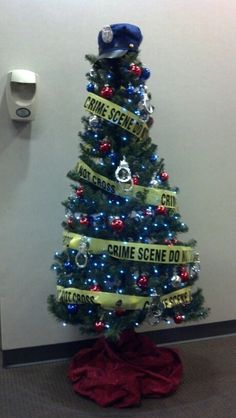 Police Christmas Tree: blue lights, red/blue/silver ornament balls, 8 silver toy handcuffs from Dollar General ($1 ea), Police crime tape, topped with blue Police costume hat found on eBay ($5.95 w/free shipping)