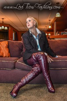 Amateur in burgundy thigh boots seated on couch
