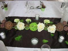 Avec vase boule contenant 2 bougies flottantes chocolat et verte, du gravier vert anis, des galets marrons et des fleurs de santini vertes...