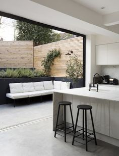 A modern, yet cosy outdoor space--- black with white cushions, and a massive door to the area.