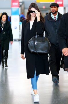 Kendall Jenner keeps it simple, arriving at the airport in cropped jeans, sneakers and a black duster coat