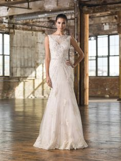 Justin Alexander Signature 9825 A geometric beaded pattern adorns this Signature fit and flare gown with a Sabrina neckline, natural waistline, and chapel length train with hem lace.