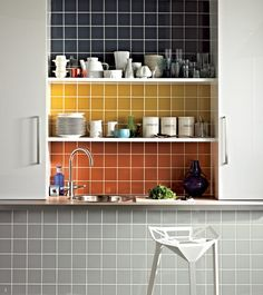 Make a feature with the same tiles used in different colours as shown here by Gemini Tiles. The shelves act as natural dividers for each colour change and the result is a very strong focal point in the alcove between the cupboards. Displaying mostly white china and accessories on the shelves keeps the look graphic and strong.