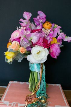 A colorful summer bouquet with ranunculus, daffodils, sweet peas, peonies, and sequin and fringe trim.