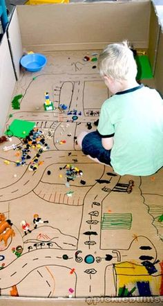 Great idea for recycling a big cardboard box! All he needs now are some little wooden cars to zoom around the streets!  Kids always like playing with boxes!  Make sure to draw some recycling dumpsters in the make - believe town!