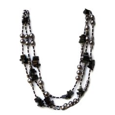 This extra long flapper necklace is handmade from natural semiprecious beads in shades of black and silver: black agate, shell pearls, and hematite.