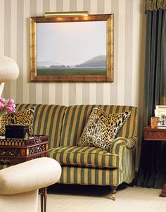 """Warm green and gold stripes on a George Smith sofa are a pleasing surprise against the muted stripes of a classic Colefax and Fowler wallpaper, """"which gives the room an English Regency feeling -- sort of genteel, but slightly shabby, too,"""" says Lysdahl. Scalamandré leopard velvet pillows. Painting above the sofa, Hamden at Dawn, by David Ryan."""