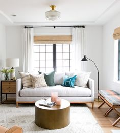 light walls, round coffee table, stools on left, clean lined sofa, light fabric, white curtains and grass or roman shades, floor lamp