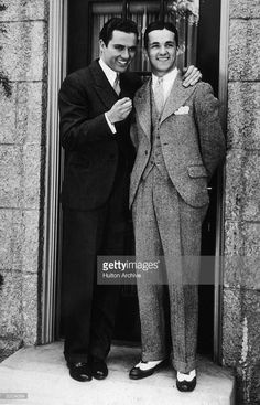 Full-length image of American actor Charles 'Buddy' Rogers (1904-1999) (L) smiling while standing in front of a doorway with his arm around his brother, B.H. Rogers, Hollywood, California. Buddy wears a pinstriped suit while his brother wears a three-piece tweed suit and spectator shoes.