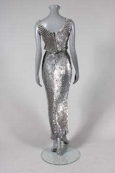 Paco Rabanne chain-mail sheath, 1970s, the knitted cotton mesh ground inter-looped with metal discs giving a fish-scale effect, with a demi-lune panel to the front bodice, figure hugging skirt with fish-tail hem, stage dress of Paco Rabanne chain-mail sheath, 1970s, the knitted cotton mesh ground inter-looped with silver metal discs giving an over-lapping fish-scale effect, with a demi-lune panel to the front bodice, figure hugging skirt with fish-tail hem, stage dress of Beatrice Argnac