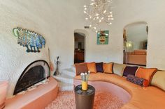 A+round+orange+banquette+offers+a+comfortable+place+to+sit+in+this+sunken+living+room.+In+addition+to+the+wired+chandelier+above,+the+burst+of+color+brightens+and+opens+the+overall+space.+Vivid+artwork+on+the+walls+and+the+Southwestern+fireplace+add+an+eclectic+touch.++++