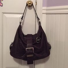 Genuine Michael Kors Leather Handbag Genuine Michael Kors Leather Handbag. Dark Purple color, Medium Size. Silver buckle on the front and on the sides of the bag. Inside is clean with no stains. Bottom of the bag has no scratches. Only used a few times, and in great condition!! Like new!! Michael Kors Bags Shoulder Bags