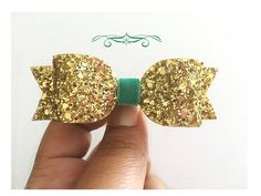 Gold and Mint Glitter Bow   Great Choice!! Our medium bows are our BEST SELLERS. Beautiful hand cut bows that are perfect for all occasions. Each piece measures approx. 3 1/2 inches wide. All glitter bows are lined with felt both at the rounded portion and also at the bottom piece.  **There are FOUR different options of hair clips available to choose from for your little ones comfort.  OR  * If you choose your piece as a headband, the elastic available is 1/8  Skinny elastic. (At no extra…