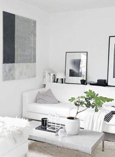 Ik hou van Scandinavisch interieur, zoals deze woonkamer. Je ziet veel wit. De bank is wit, de muren, de vloer en de hocker zijn wit. Met verschillende kleuraccenten wordt er sfeer in het huis gebracht, hier met verschillende tinten grijs (zoals de salontafel en de kussens).