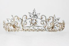 Lovely delicate scrolls and marquise crystal stones create this regal bridal tiara. Sure to make a statement on your wedding day! It is 2.25 inches high and the decoration is 11 inches long.