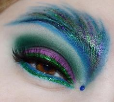 Vibrant peacock inspired make-up with a single blue crystal accent.