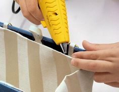 To attach the lining made in Step 1, remove any pins and apply hot glue to all four of the fabric's folded-under edges. Press the lining to the covers' interior, starting at the top edges and working down toward the spine.   - CountryLiving.com