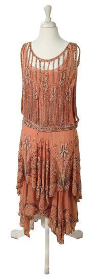 1920's Coral Chiffon Flapper Dress. The dress has a dropped waist above a double-tiered skirt and is decorated with elaborate silver and white beads.
