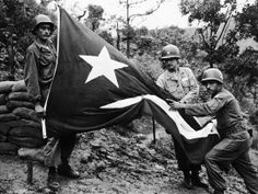 Sgt. Carmelo C. Mathews (left) holds up a Puerto Rican flag riddled by enemy shellfire, as Pfc. Angel Perales (right) points to the protrudi...