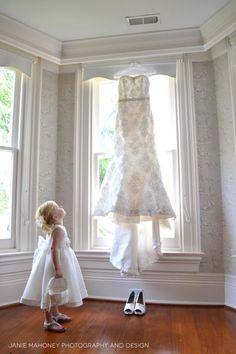 Flower Girl Looks At Wedding Dress In Window