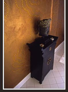 black chinese style table & buddha head with gold details against textured gold wall