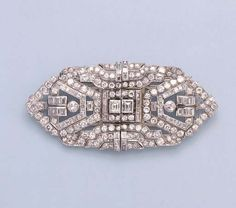 AN ART DECO DIAMOND DOUBLE-CLIP BROOCH  Each openwork clip designed with pavé-set and baguette-cut diamond geometric patterns to the central rectangular-cut diamond collet, circa 1930, 9.0 cm. wide