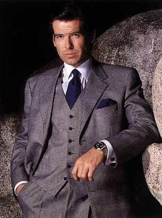 Pierce Brosnan in classic collarless vest 3-piece, with accompanying pocket handkerchief.