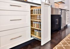 Smart storage solutions by CliqStudios keeps your kitchen organized with features such as this base cabinet with pull-out spice rack, shown here in Dayton shaker cabinet style in painted White finish.