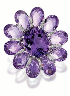 AMETHYST AND DIAMOND BROOCH, MICHELE DELLA VALLE   A brooch modelled as a large flower head, centring on a cushion-shaped amethyst of rich purple hue, encircled by facetted amethyst petals, interspersed by tapered lines of pavé-set brilliant-cut diamonds, mounted in 18 karat white gold; signed.