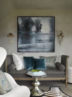 French settee daybed upholstered in charcoal gray linen fabric, blue velvet pillows, blue & gold damask pillows, zebra cowhide rug, octagon accent table, art and Venetian plaster walls.