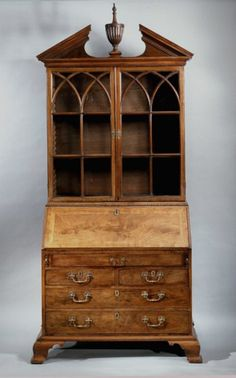 George III Mahogany bureau bookcase circa 1765. This bureau has a number of anomalous features for its date including the well, the neo-classical style finial, the Gothick doors and the fact that the slant front is a solid slab of high grade crotch mahogany. The exceptional quality of the whole relates to work by Gillows of Lancaster.      Height: 9 feet 2 inches  Width: 47 inches  Depth: 27 inches