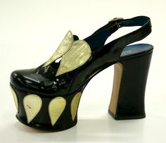 1970s Italian platform slingback shoe with black patent leather uppers, featuring gold leather inverted teardrop motifs at throat. Platform shoe and heel, also covered with black patent leather; the sole is further decorated with a row of gold leather teardrop motifs.