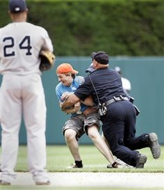 GAME 53: Sunday, June 3, 2012 - A Detroit policeman tackles a spectator who ran onto the field at Comerica Park as New York Yankees' Robinson Cano (24) looks on in the ninth inning of a baseball game against the Detroit Tigers in Detroit. The Yankees defeated the Tigers 5-1. (AP Photo/Duane Burleson)