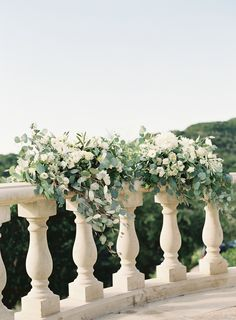 Ceremony Garland on balcony at Villa Del Lago. Image by Mint Photography. #whiteflowers #sagegreenery #ceremonyfloral #rail #garland