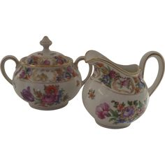 Vintage creamer and sugar by Dresden Dresdner Art Schumann Bavaria. Floral bouquets with gold trim. Measures creamer 4 1/2 by 4, sugar 6 by 4. There
