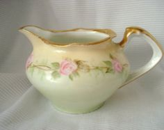 Vintage Shabby Limoges Jean Pouyat France Creamer Handpainted Pink Roses and Turquoise Vintage  This is a sweet little creamer from Jean Pouyat Limoges (J.P.L) France that features a white background accented by handpainted festoons of pink roses, tiny blue flowers and green foliage. The rim of the creamer has a gorgeous turquoise blue border. The handle is burnished gold, as well as the trim at the top edge of the creamer. Tiny gold bows are also handpainted around the top border. The…
