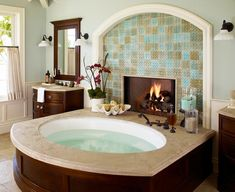Tiled fireplace next to a nice big spa bath tub... so relaxing! #design #decor #home #bathroom #interiors