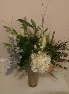 A classy golden arrangement completed with a stunning white hydrangea.