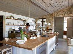 La cuisine-atelier d'Isabella est vaste, lumineuse. Béton ciré, peinture gris satiné et Inox sont réchauffés par un mur de pierres et du bois blond.