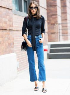 A black t-shirt is worn with cropped flare jeans, black sandals, and a skinny scarf
