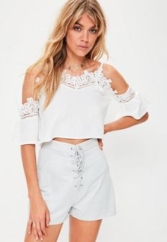 72338a78f5c20 Cold shoulder top in a white hue with crochet trims and a swing style.  Finished