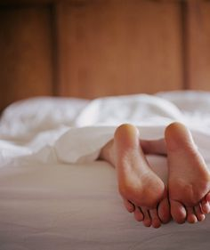 Woman sticking foot out of bed | And expert-approved advice to rest well, anyway.