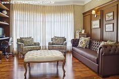Painel e móvel de madeira conferiram sobriedade ao escritório. O ar clássico ficou por conta do sofá (Artenal) e pufe capitonê (Jackie)