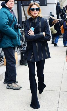 Olivia Palermo wears a striped blazer, skinny flare pants, and turquoise frame sunglasses