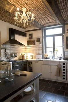 Exposed brick and wood beam ceiling with chandelier in kitchen. Very rustic glam