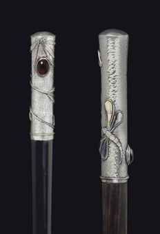 Glass-mounted silver canes. Late 19th/early 20th Century. With hand-hammered ground, one decorated with stylized bamboo and glass cabochons above an ebonized shaft, the other French and with mother of pearl dragonflies and vines above an ebony shaft