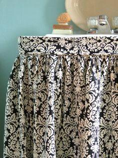 Hide Clutter With a Sink Skirt  Pedestal sinks are ideal for tight spaces but often show exposed plumbing and offer little storage. An easy-to-sew sink skirt will solve both problems, providing style and function to a bathroom. Choose a trendy, patterned fabric, like damask, ikat or suzani, for maximum visual impact.