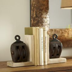 Hoist Bookends   Keep books in line with this sturdy pair of pulley-shaped bookends crafted from mango wood and iron. Set of two.