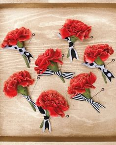 Carnation boutonnieres knotted with graphic ribbons